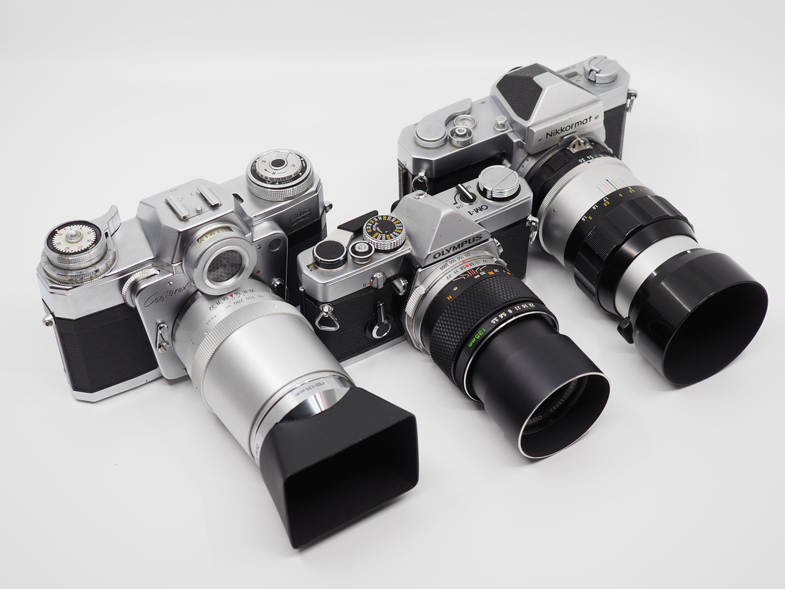 A few 135mm lenses that I own, from left to right: Carl Zeiss 135mm Planar on the Zeiss Contarex Bullseye,Olympus 135mm E.Zuiko on a OM-1 and the Nikon Nikkor-Q 135mm on a Nikkormat FT-N.